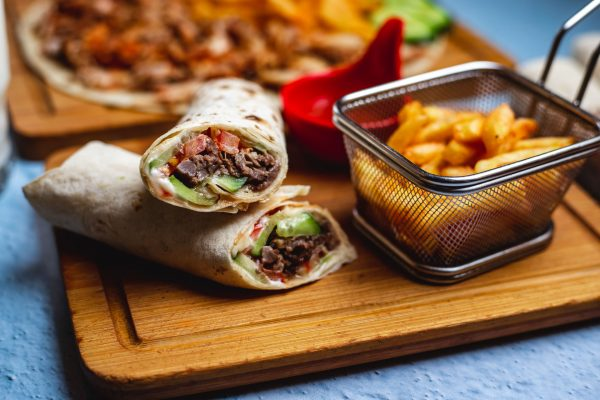 side view doner with meat cucumber tomato sauce and french fries on a board